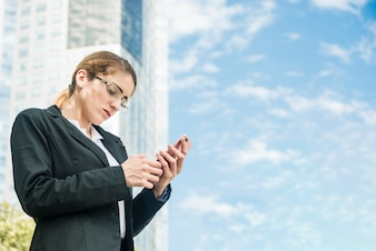 Young businesswoman standing in front of building texting message on mobile phone