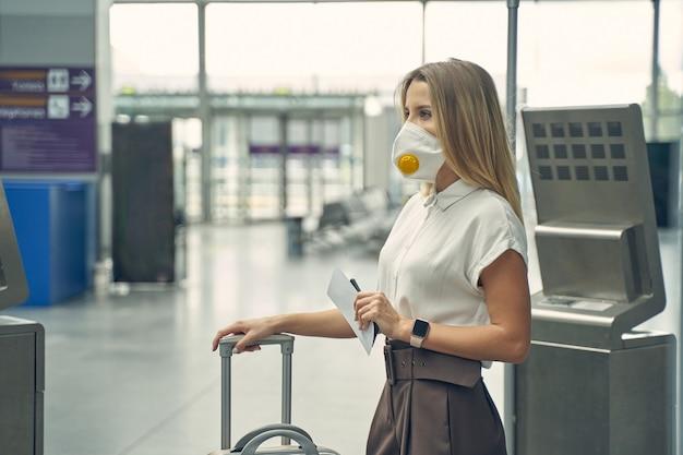 セミポジションに立って、到着と出発のモニターを見ながら彼女のチケットを保持している若い実業家