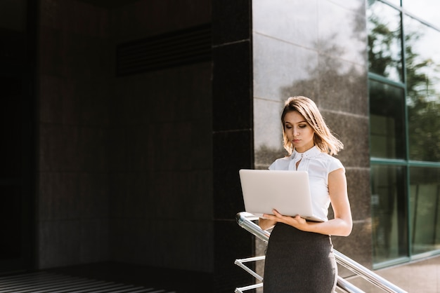 Young businesswoman standing outside the office using laptop