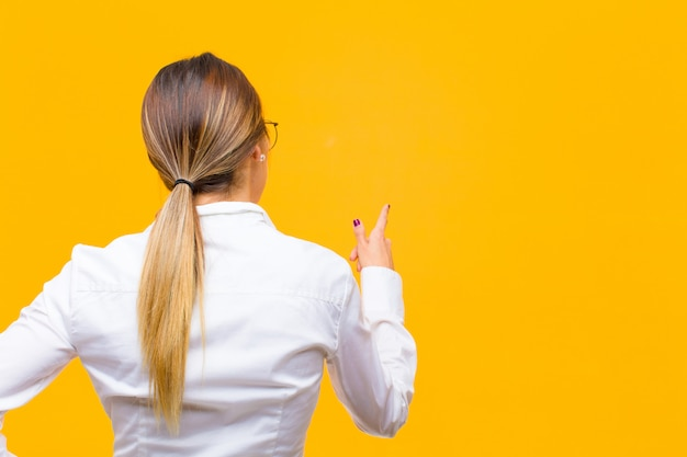 Young businesswoman standing and pointing to object on copy space, rear view over orange wall