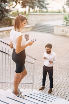 Young businesswoman standing on staircase using smartphone while businessman looking at digital tablet