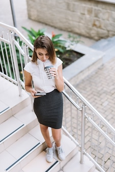 Young businesswoman standing on staircase using smartphone