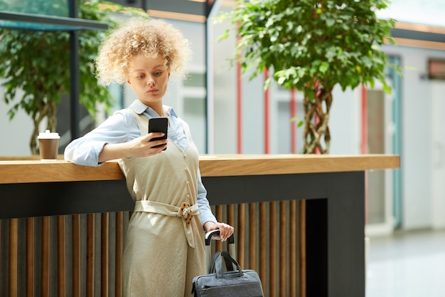 Young businesswoman standing with suitcase and using mobile phone while drinking coffee in coffee shop