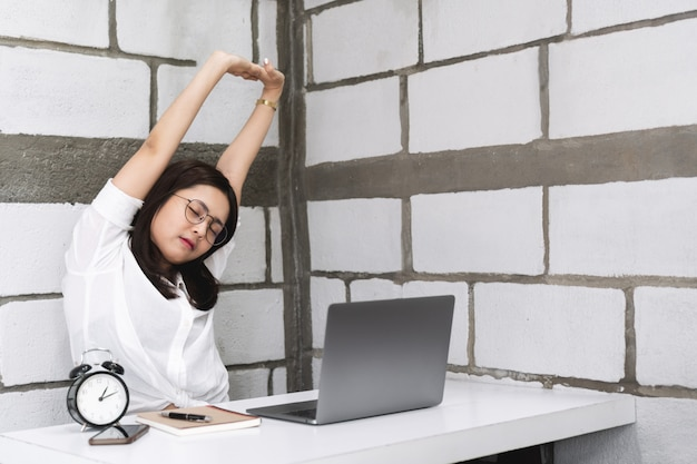 Young businesswoman stretching her arms and body for relaxing while working in office with laptop.