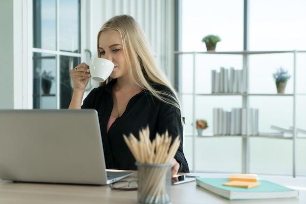 Молодой предприниматель студент-фрилансер пьет кофе во время работы на домашнем офисном столе