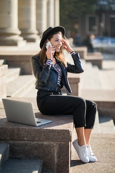 젊은 사업가 학생 소녀는 도심에서 그녀의 브랜드 노트북 컴퓨터와 함께 작동