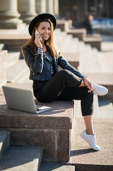 若い実業家の学生の女の子は、市内中心部で彼女のブランドのラップトップコンピューターで動作します