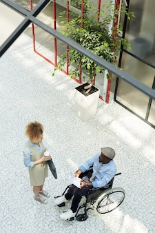 Young businesswoman talking to african disabled businessman in wheelchair while they are at office corridor