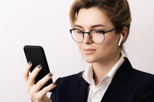 灰色のワイヤレス イヤホンを使用して電話で話している若い実業家