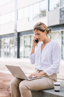 Young businesswoman talking on mobile phone using laptop