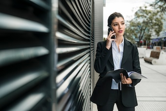 Young businesswoman talking on mobile phone holding folder in hand looking away