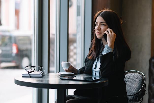コーヒーショップで電話で話している若い実業家