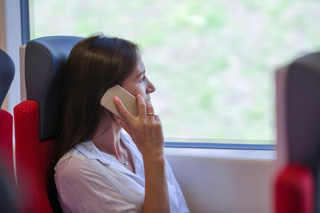 Young businesswoman talking on the phone traveling by train