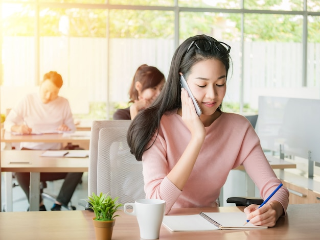 Young businesswoman talking on smartphone and using writing on notebook