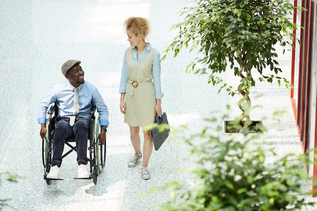 사무실 복도에서 휠체어에 장애인 된 동료와 이야기하는 젊은 사업가
