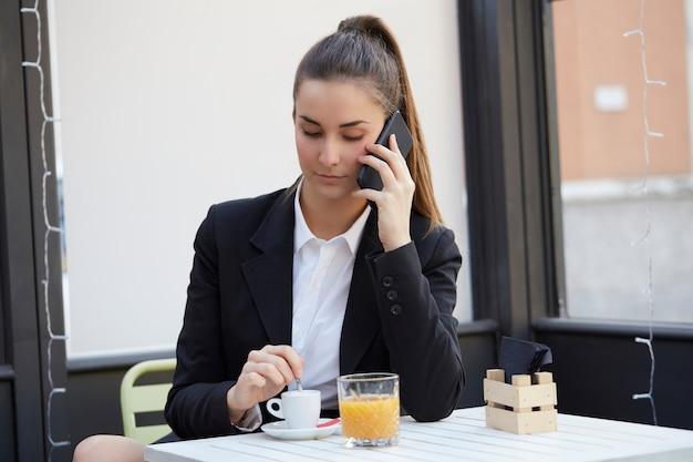 Молодая коммерсантка говоря к черни и выпивает чашку кофе