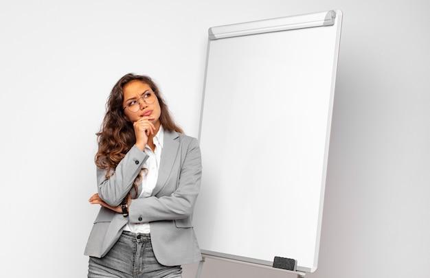 Молодая деловая женщина думает, сомневается и сбивается с толку, с разными вариантами, задается вопросом, какое решение принять