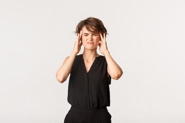 こめかみに触れ、痛みを伴う片頭痛から顔をゆがめた若い実業家。頭痛を訴える少女、白く立っている。
