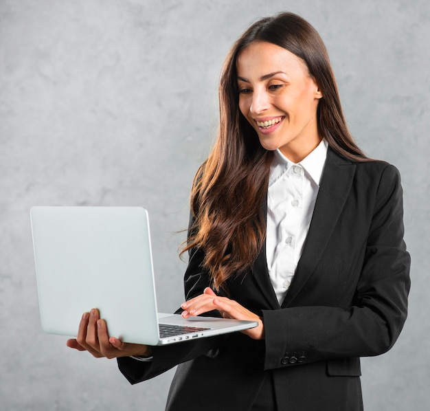Young businesswoman typing on laptop standing against gray background