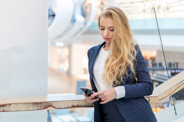 Young businesswoman using her smartphone to browse web content and sending messages