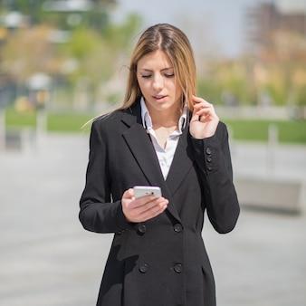 屋外でスマートフォンを使用している若い実業家