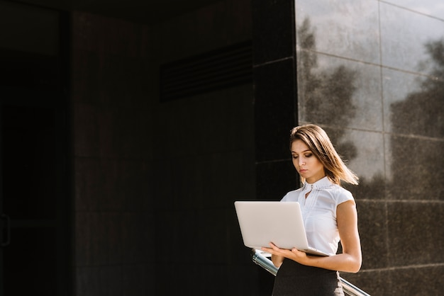 Young businesswoman using laptop standing outside the building