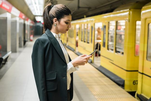 Молодая коммерсантка используя мобильный телефон стоя на станции метро