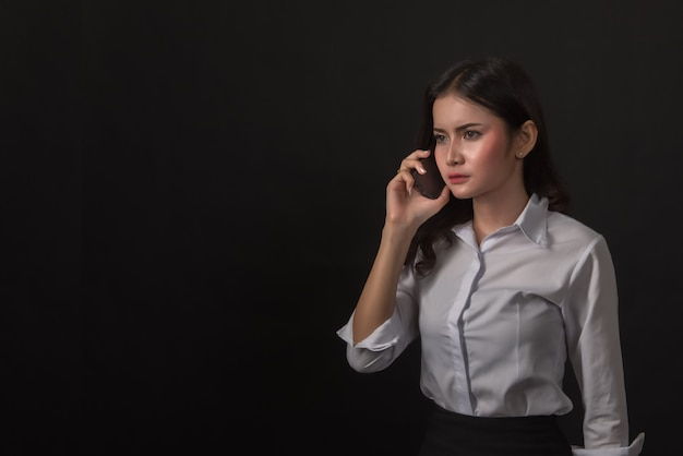 Young businesswoman using phone on black.