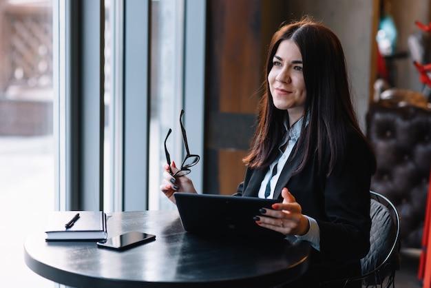 コーヒーショップでタブレットコンピューターを使用して若い実業家