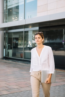 Young businesswoman walking in front of corporate building
