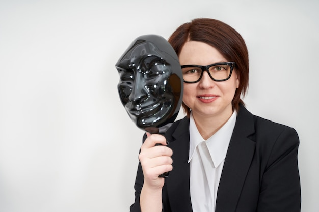 Young businesswoman wearing black formal suit standing and holding black plastic mask, hiding concept with copy space