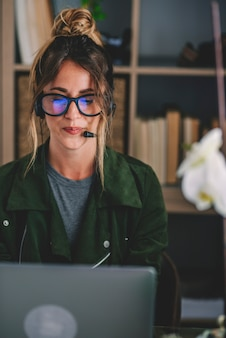 Молодой предприниматель в очках и гарнитуре при использовании ноутбука на рабочем месте, красивая женщина с помощью ноутбука. женщина в наушниках с микрофоном, глядя на экран ноутбука