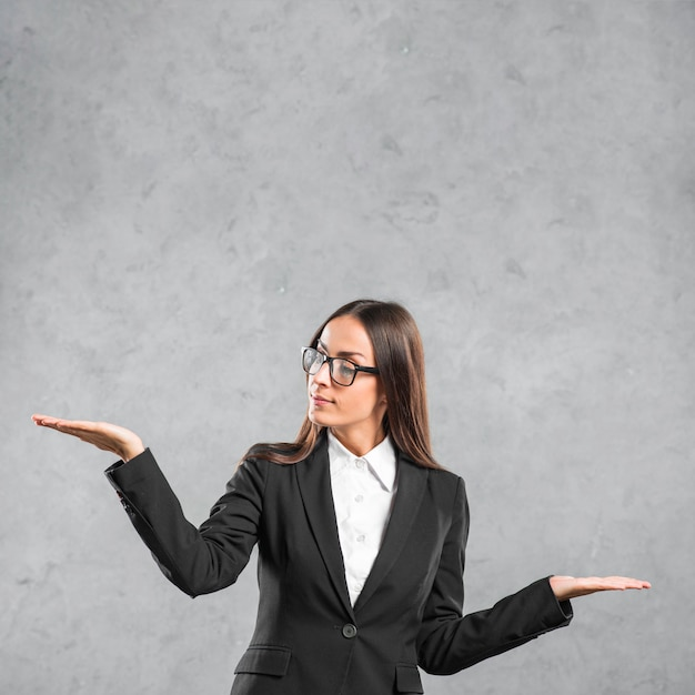 Young businesswoman wearing eyeglasses presenting against grey background