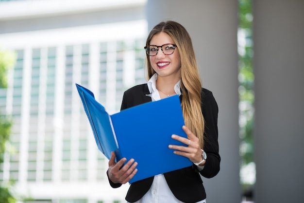 Young businesswoman wearing eyeglasses and reading documents outdoor in a modern urban setting