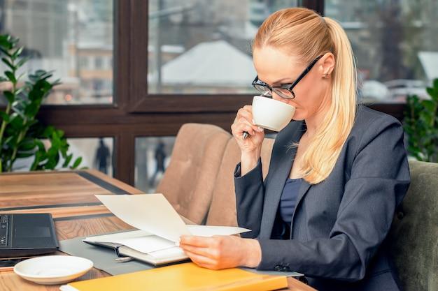 Стекла молодой коммерсантки нося сидя в кофейне на таблице читает документы перед компьтер-книжкой и выпивая кофе.