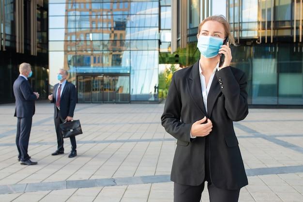 Giovane imprenditrice indossando maschera e tuta da ufficio parlando sul cellulare all'aperto. uomini d'affari ed edifici della città in background. copia spazio. concetto di affari ed epidemia