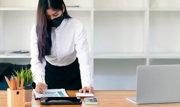 Молодой предприниматель в медицинской маске, работая над документами, стоя за своим офисным столом.