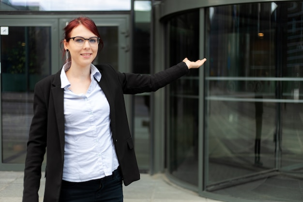 Young businesswoman welcoming you in a modern city setting