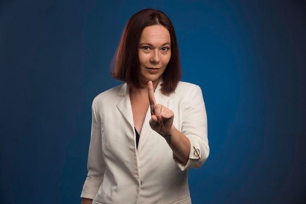 La giovane donna di affari in giacca sportiva bianca chiede attenzione.