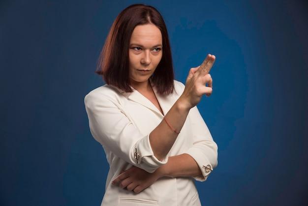 Giovane imprenditrice in giacca sportiva bianca facendo forma di pistola.