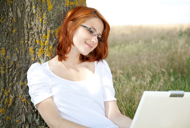 Young businesswoman in white with glasses and laptop sitting near tree.