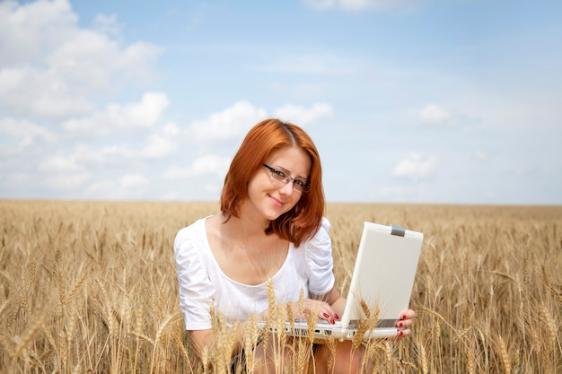 Young businesswoman in white working with notebook at wheat field.