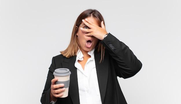 Молодая деловая женщина с кофе выглядит потрясенной, напуганной или напуганной, закрывая лицо рукой и выглядывая между пальцами