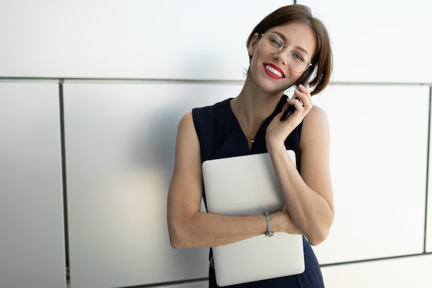 전화 통화하는 그녀의 손에 노트북과 젊은 사업가. 회색 벽 배경에 비즈니스 초상화