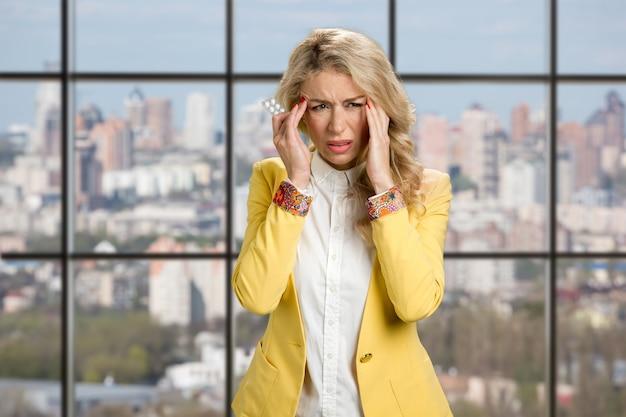 ひどい頭痛のある若い実業家。オフィスの窓に薬の丸薬を保持している頭痛に苦しんでいる美しい女性