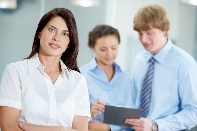 Молодой предприниматель с коллегами фоне
