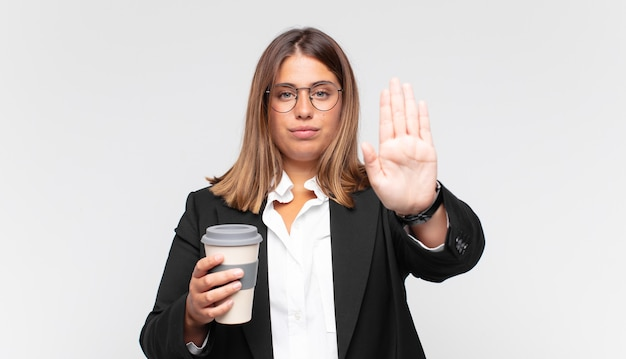 Young businesswoman with a coffee looking serious, stern, displeased and angry showing open palm making stop gesture Premium Photo