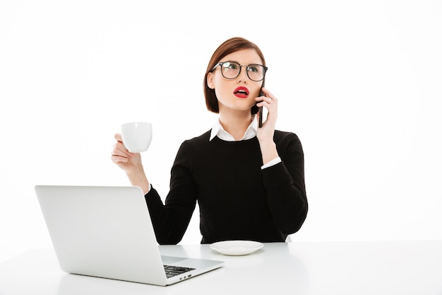Young businesswoman with coffee or tea cup and laptop computer, talking by phone