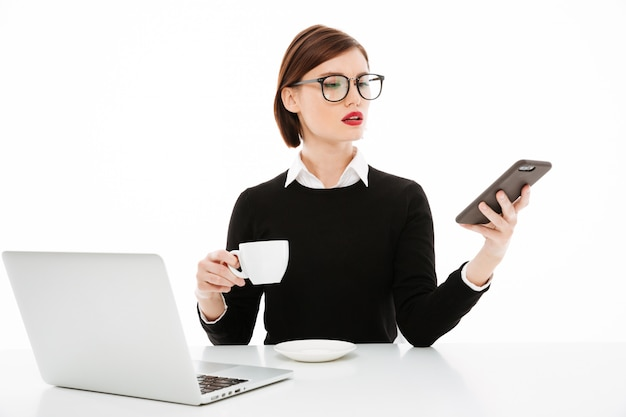 Young businesswoman with coffee or tea cup and laptop computer, using smartphone