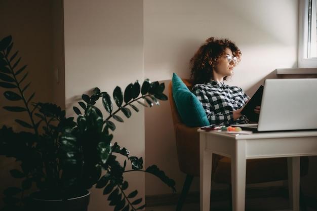 本を持っている間何かを考えているコンピュータで自宅で仕事をしている巻き毛と眼鏡を持つ若い実業家